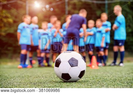 Soccer Ball And Blurred Youth Soccer Team With Coach On The Field