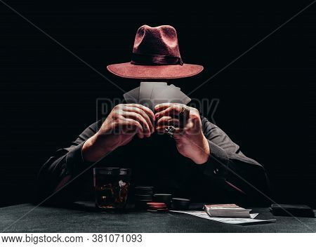 Photo of a shaded gangster in black shirt and hat playing poker and game chips and money.