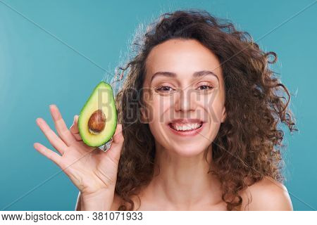 Young beautiful and joyful woman with luxurious wavy hair looking at you with toothy smile while holding half of fresh avocado in hand