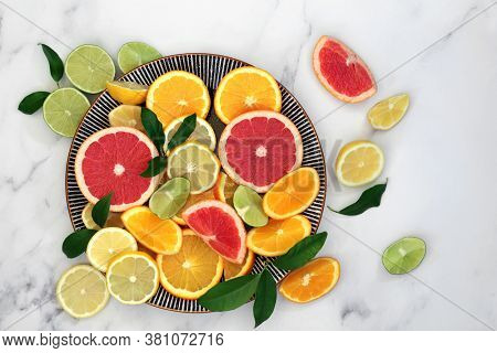 Immune boosting citrus fruit health food with orange, lemon, grapefruit &   leaves on round plate and marble background. Super foods high in antioxidants, vitamins, dietary fibre & anthocaynins.