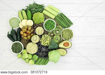 Vegan health food with plant based green vegetables and fruit on rustic wood  Foods high in protein, vitamins, minerals, antioxidants and dietary fibre. Healthy ethical eating concept. Flat lay.