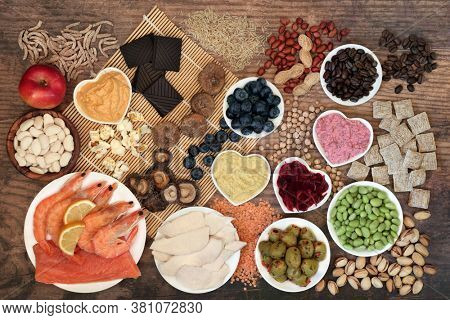 Health food for vitality & fitness with foods high in vitamins, minerals, anthocyanins, antioxidants, smart carbs, protein & omega 3. Flat lay on bamboo mat and rustic wood.