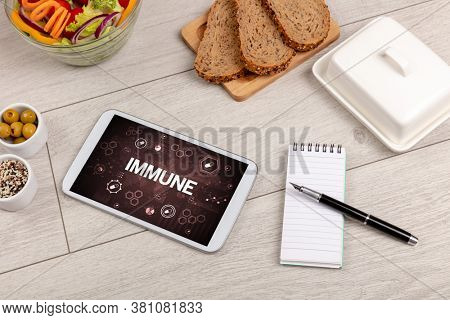 Healthy Tablet Pc compostion with IMMUNE inscription, immune system boost concept