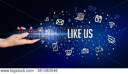 hand holding wireless peripheral with LIKE US inscription, social media concept