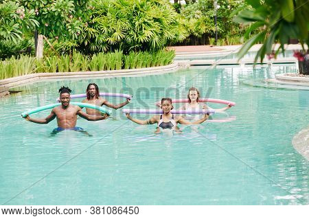 Multi-ethnic Young People Doing Water Aerobics With Floating Noodles In Swimming Pool Of Hotel
