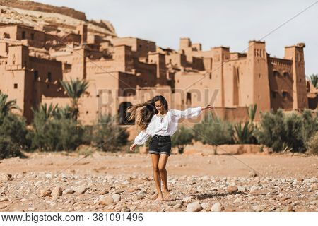 Young Curly Woman Eastern Appearance Walking On Background Of Kasbah Ait-ben-haddou. Travel In Moroc