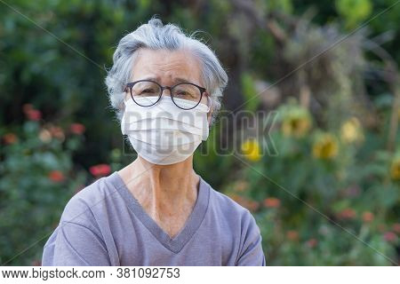 A Portrait Of An Elderly Woman Wearing A Mask While Standing In A Garden. Mask For Protect Virus, Ba