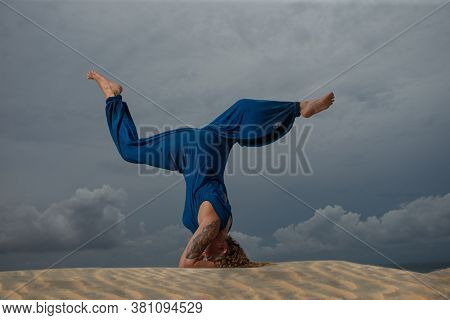 Young attractive woman practicing yoga, standing in Sirsasana pose (Supported Head Stand), wearing in blue jumpsuit, side view in the beach against cloudy sky.
