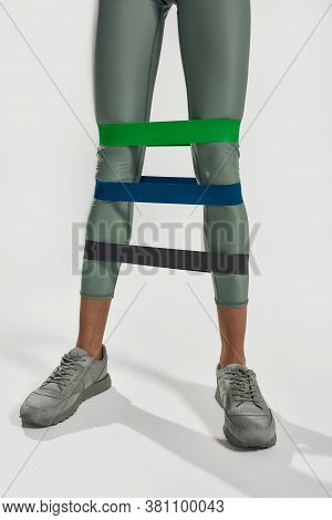 Strong Legs. Close Up Of Legs Of Sportive Woman Doing Leg Exercises Using Fitness Gum, Three Elastic