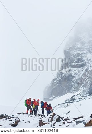 Hikers Team Standing On Rocky Path Near High Mountain Covered With Snow. Male Travelers With Backpac