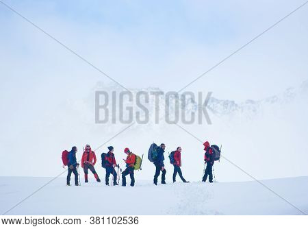Hikers Team With Backpacks Standing On Hillside Valley Covered With Snow, Admiring The View Of Winte