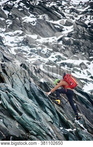 Side View Of Alpinist With Backpack Using Rope While Climbing Alpine Ridge. Male Climber Ascending M