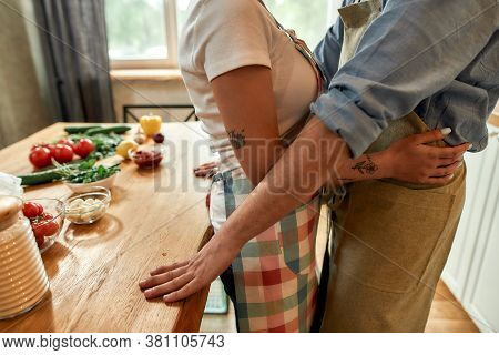 Embrace. Cropped Shot Of Man And Woman Embracing While Standing In The Kitchen. Couple Hugging While