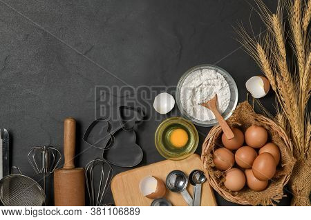 Fresh Eggs And Cake Flour  With Kitchen Utensils For Pastries On Black Table, Prepare For Make Cake