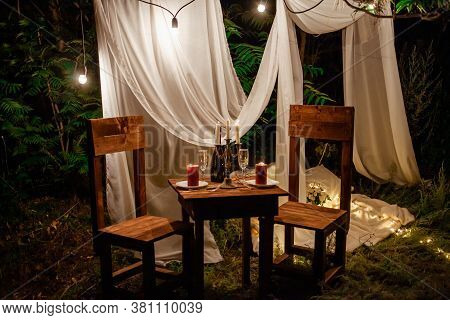 Table In The Woods, Romantic Dinner For Two By Candlelight. White Curtains On The Tree, A Garland Of