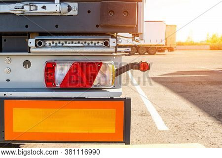 Truck Driver Semitrailer Rear View, Warning Lights And Long Length Signs On The Trailer. Concept Of