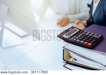 Calculator And Binders With Papers Are Waiting To Be Processed By Business Woman Or Bookkeeper Worki
