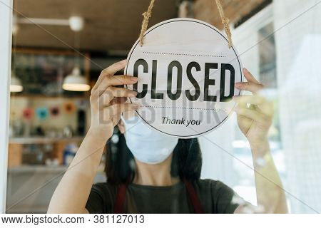 Closed. Waitress Woman Wearing Protection Face Mask Turning Close Sign Board On Glass Door In Modern