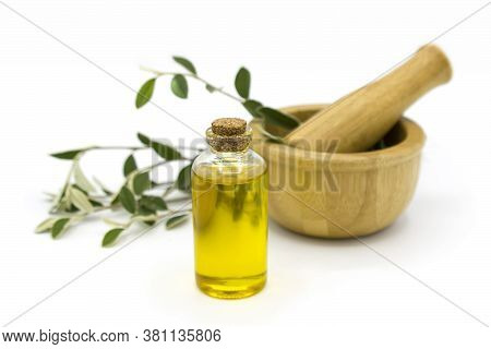 Small Bottle With Natural Herbal Oil And Wooden Mortar With Herbs On White Background. Alternative A