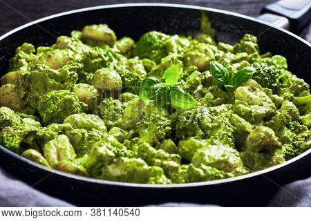 Italian Gnocchi With Broccoli Florets Tossed With Basil Pesto And Creamy Cheese Sauce In A Skillet,