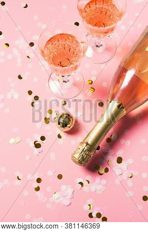 Bottle Of Rose Sparkling Wine Or Champagne On Pink Background With Wineglass, Confetti And Christmas