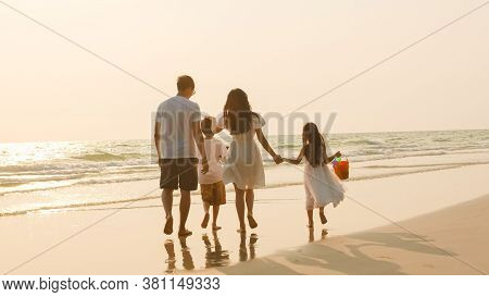 Asian Young Happy Family Enjoy Vacation On Beach In Evening. Dad, Mom And Kid Relax Walking Together