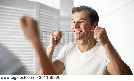 Oral Hygiene Concept. Closeup Portrait Of Guy Using Dental Floss Looking In The Mirror, Banner