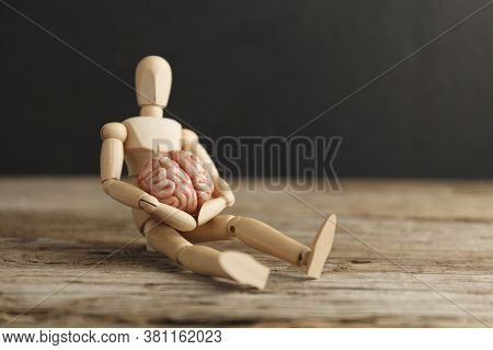 Toy Man Holds An Anatomical Brain In His Hands. Care And Therapy, Psychological Symptoms. Neuroligic