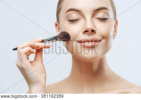 Close Up Portrait Of Beautiful Girl Has Fresh Healthy Skin, Closes Eyes, Applies Cosmetics On Face,