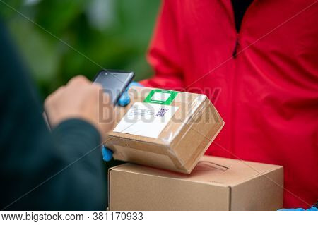 Male Customer Scanning Bar With Phone Code To Receive Products From Delivery Man
