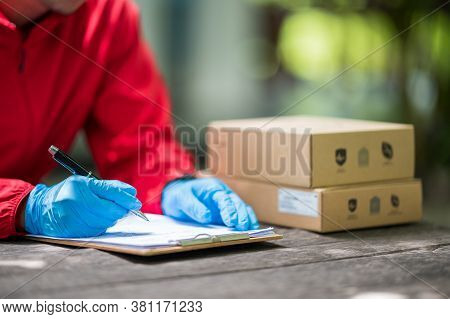 Close Up Delivery Man Wearing Blue Gloves In Red Cloth Checking Customer Boxes For Delivery