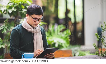 Men Use Tablets To Check Business Emails At Coffee Shops.