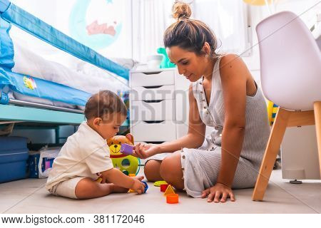 Young Caucasian Mother Playing With Her In The Room With Toys. Baby Less Than A Year Learning The Fi