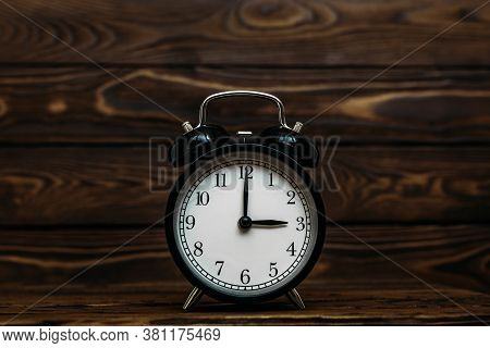 Clock On A Wooden Background. The Clock Shows The Time Of Three O'clock In The Afternoon. The Clock