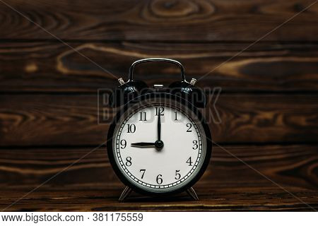 Clock On A Wooden Background. The Clock Shows The Time Of Nine O'clock In The Afternoon. The Clock S
