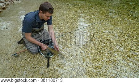 Catch And Release - A Rainbow Trout Fish Being Released Back Into A River, By A Fisherman On The Soc