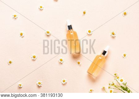 Glass Bottles Of Essence Or Serum With Chamomile Flowers.