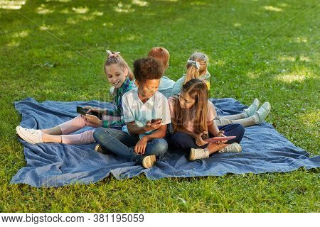 High Angle View At Multi-ethnic Group Of Kids Using Gadgets While Sitting On Green Grass In Park Out