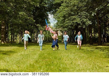 Wide Angle View At Multi-ethnic Group Of Kids Running Towards Camera Across Green Lawn With Girl Wav