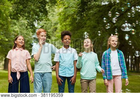 Front View Portrait Of Multi-ethnic Group Of Kids Standing In Row Outdoors While Playing With Bubble