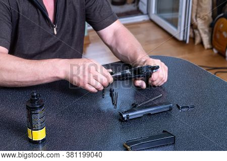 Lubricating The Gun At Home. Maintenance Of The Gun At Home. Weapon Care. The Man Is Cleaning The Gu