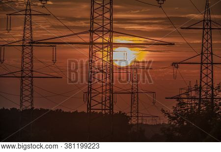 Power Poles In Front Of Sunset In Backlight