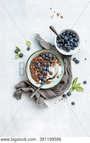 Granola And Blueberry Breakfast With Plain Yogurt Served In A Bowl, Overhead View