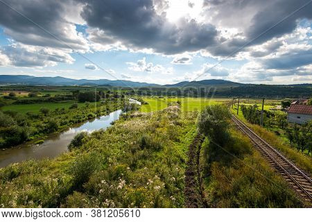 View From A Bridge, Olt River Near Railroad Tracks Curving In Opposite Direction At Early Summer, Dr