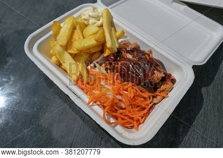 Pulled Pork In A Take Away Box With Barbecue Sauce, Coleslaw And Carrot Salad, French Fries And Mayo