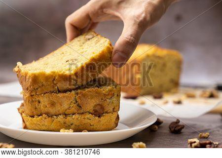 Hand Hold A Slice Of Banana Walnut Pound Cake To Show Its Softness