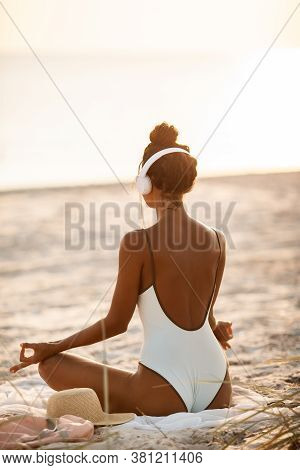 Woman Meditation On The Nature. Young Beautiful Woman In Bikini Meditating And Listening To Calm Mus