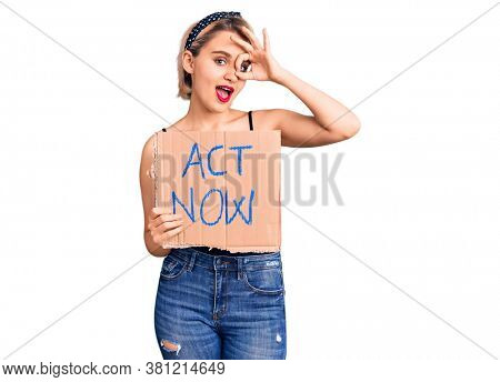 Young beautiful blonde woman holding act now banner smiling happy doing ok sign with hand on eye looking through fingers
