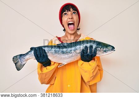 Beautiful brunettte fisher woman wearing raincoat holding fresh salmon angry and mad screaming frustrated and furious, shouting with anger looking up.