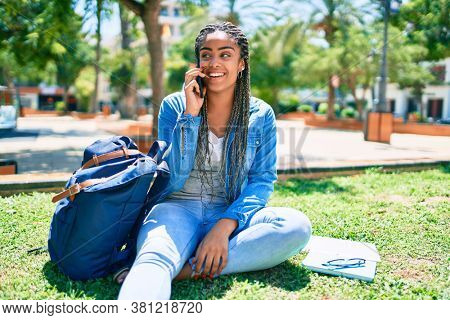 Young african american student woman smiling happy speaking on smartphone sitting on the grass at the university campus